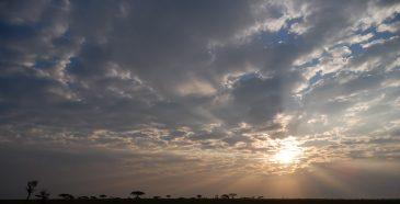 African sun bursts through cloudy sky