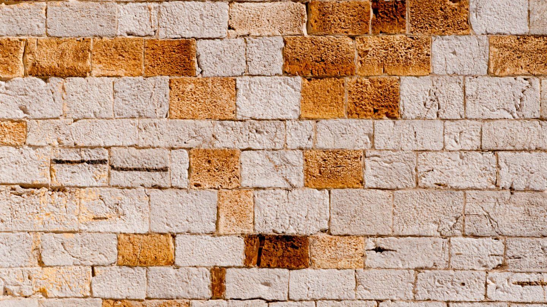 Big stone wall with random pattern of orange colored bricks