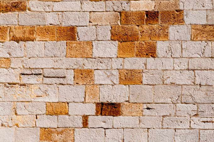 Big stone wall with random pattern of orange colored bricks