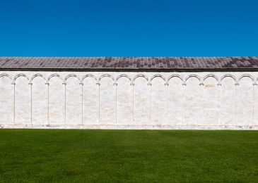 Blue sky, white medieval wall, green grass