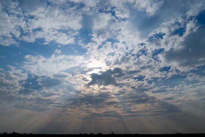 Fullframe sunbeams piercing cloudy sky