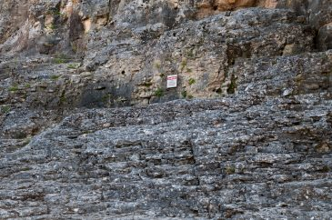 Mountain steep surface with small danger sign
