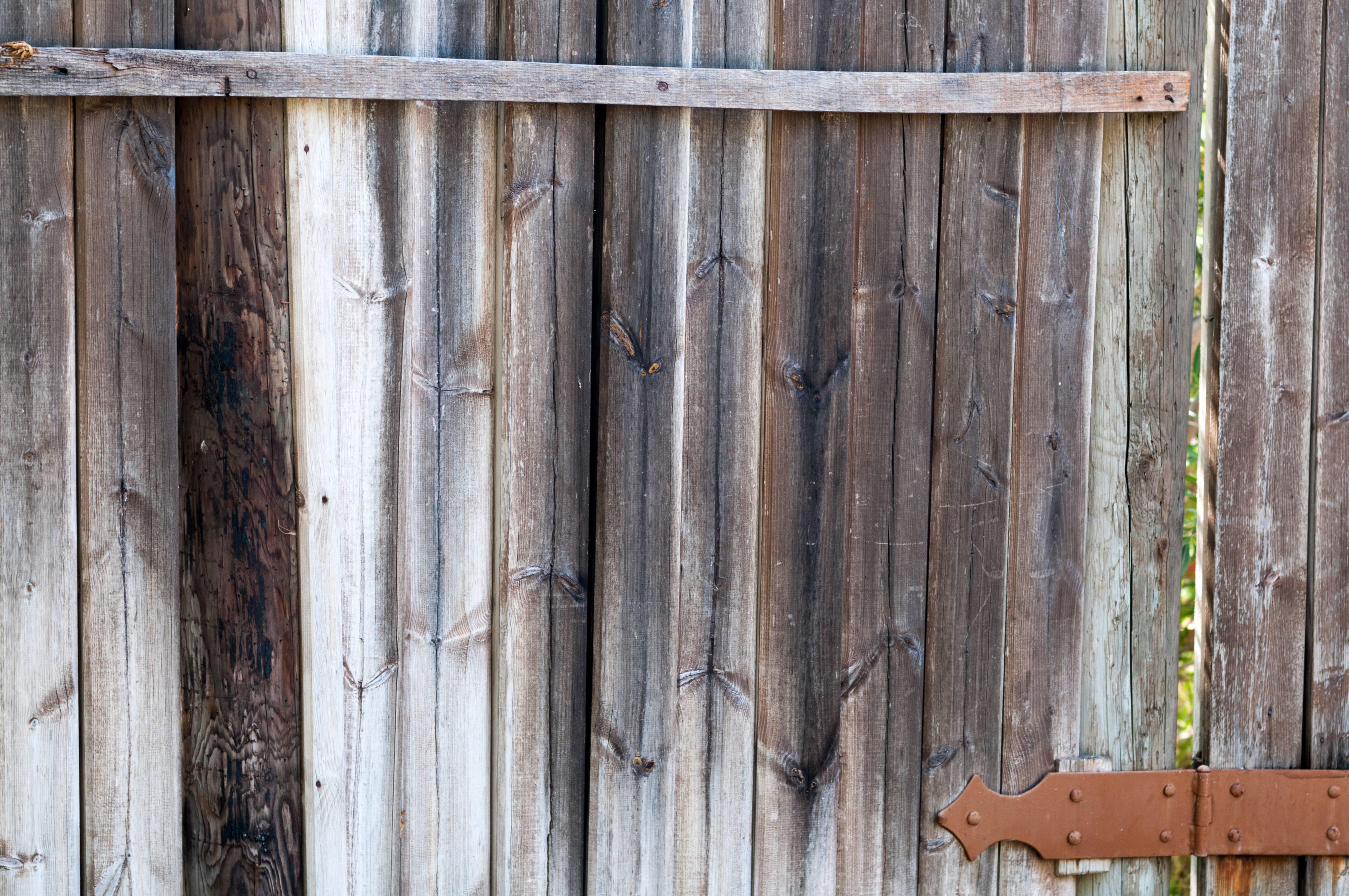 Old wooden door with a rusty hinge