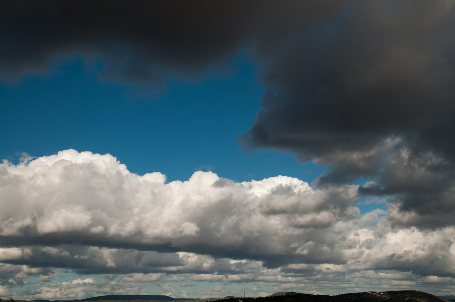 White and dark grey clouds with blue sky