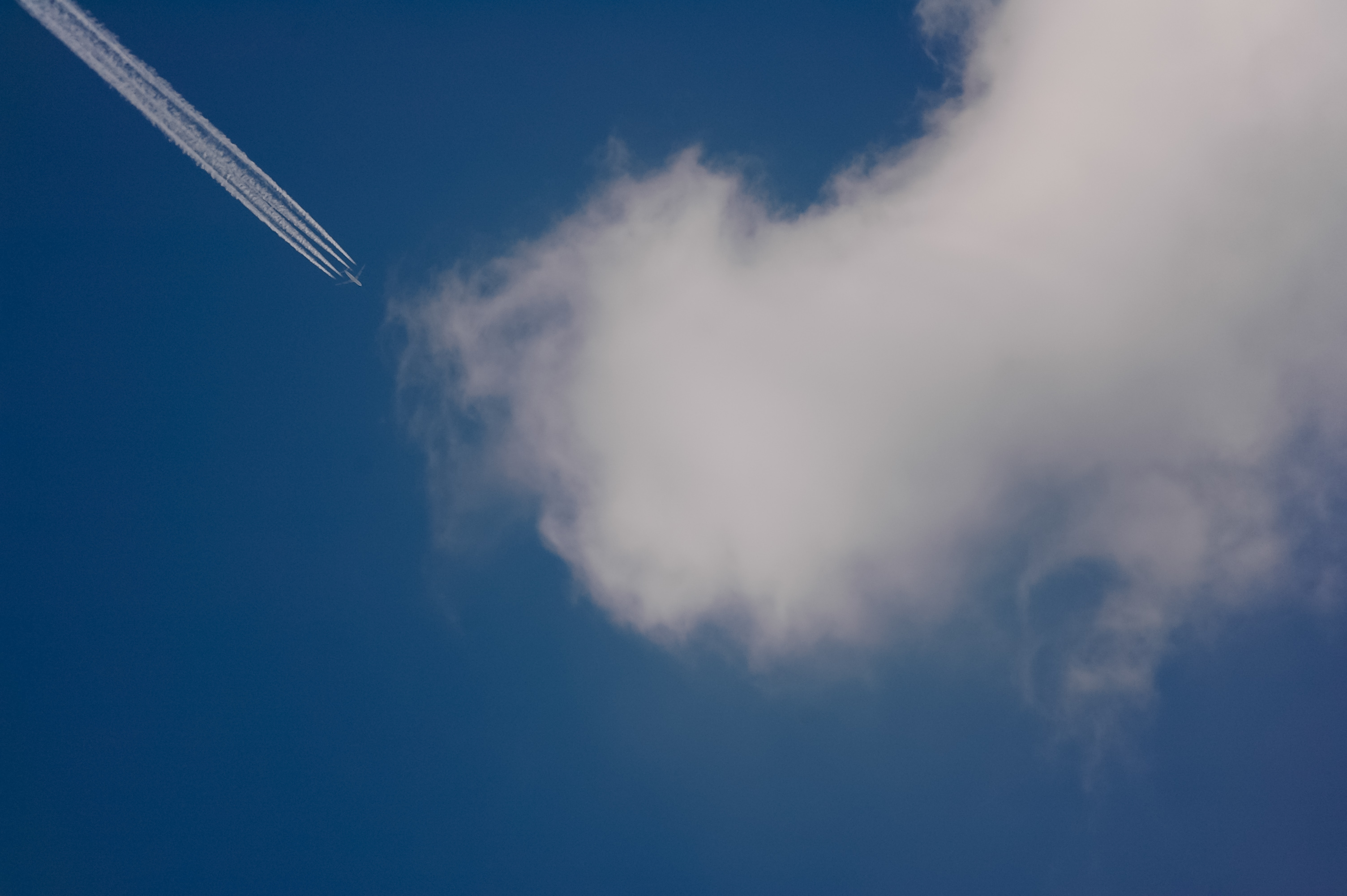 White cloud trail from jet flying high in the sky
