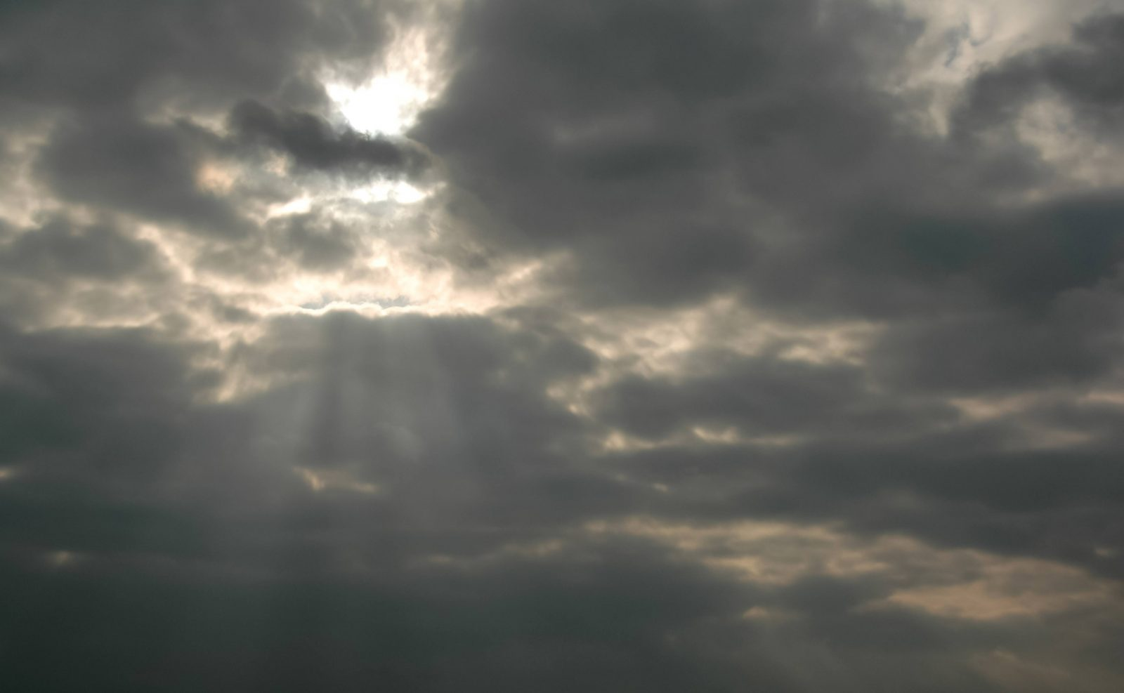 Sun beams through a dark cloudy sky
