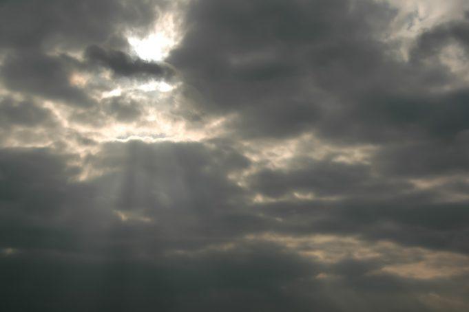 Sun beams through a dark cloudy sky