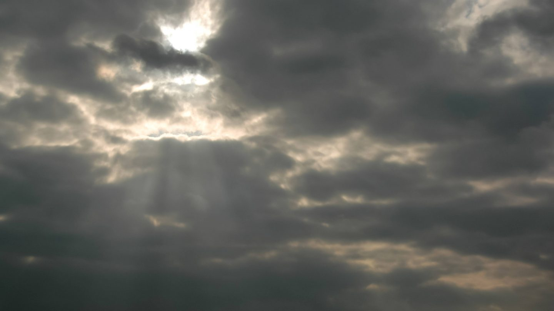 Sunbeams burst through dark clouds