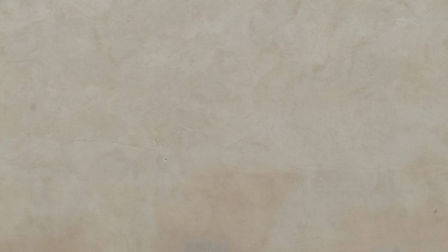 Warm white colored subtle grain plastered wall