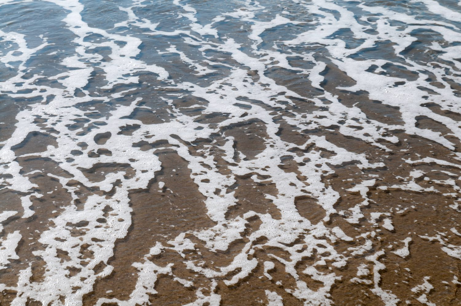 Water foam bubbles on the beach surface textured background