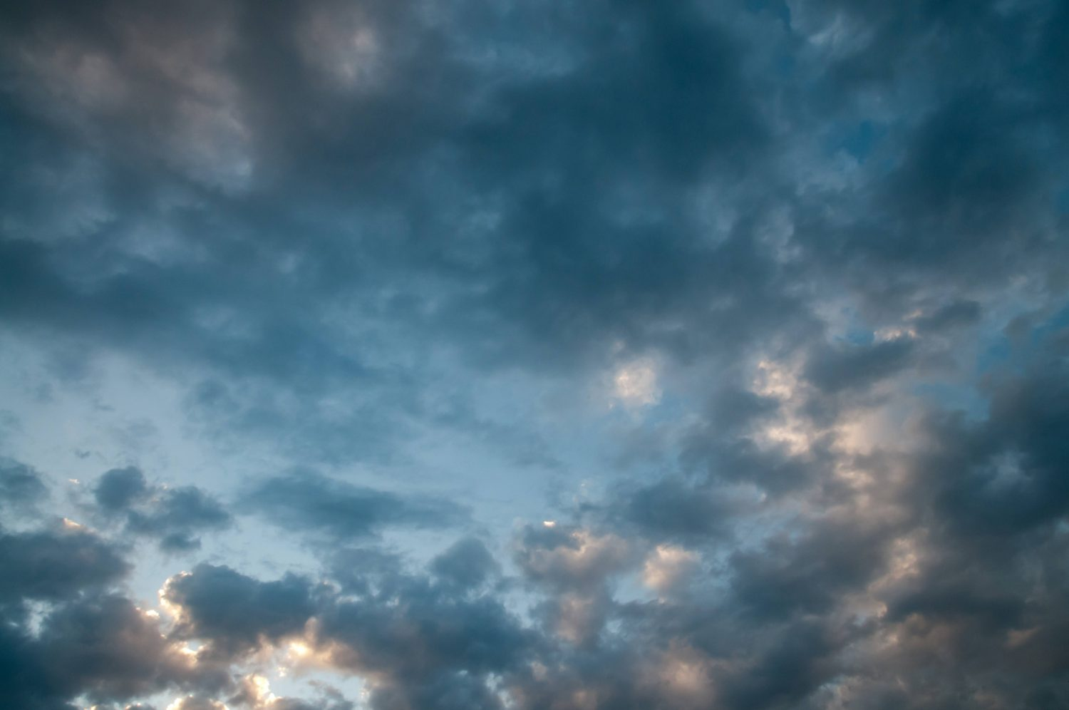Dark small clouds in front of blue sky